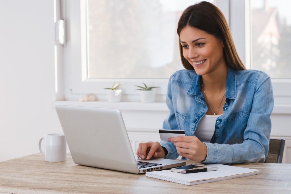 Woman holding credit card purchasing online