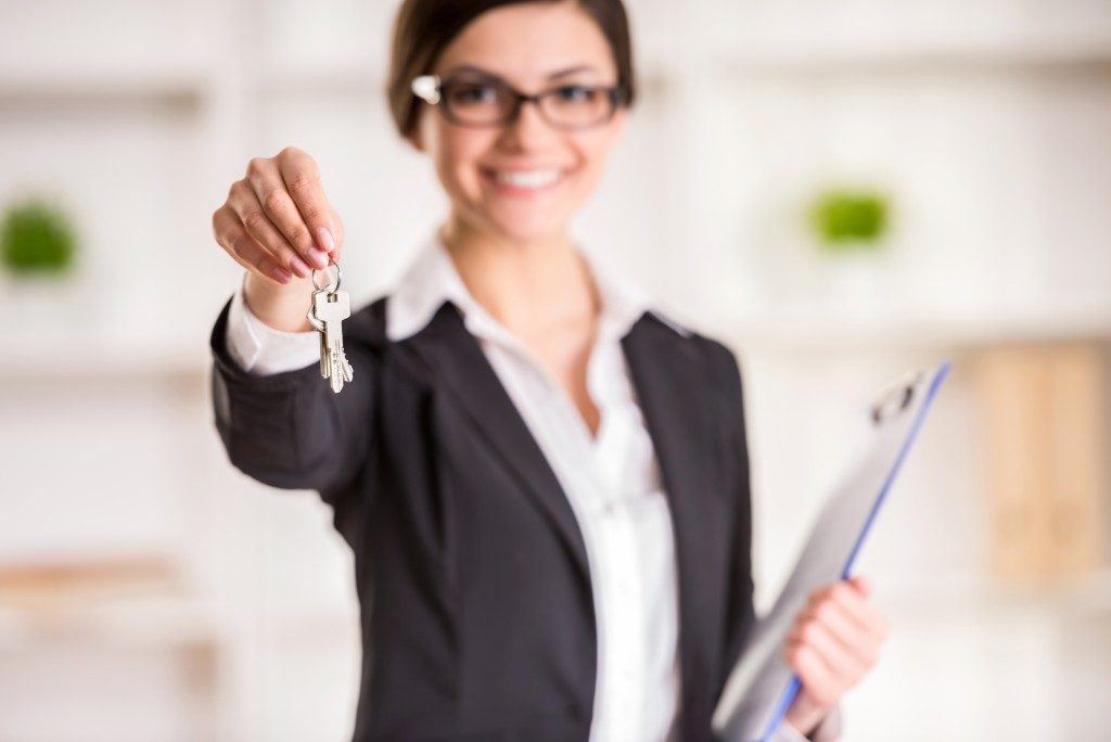 woman is holding the keys to an apartment to clients
