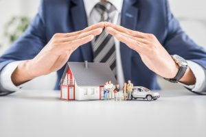 Business man with hands covering home figure