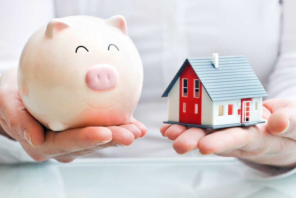 Man holding a piggy bank and a house model