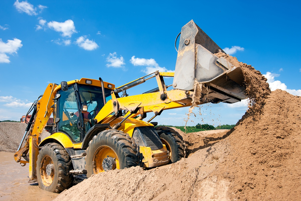 Backhoe loader being used to unload soil by worker
