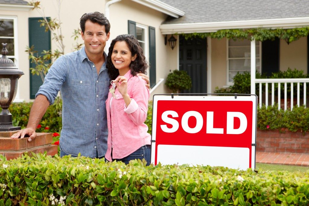couple outside new home with sold sign