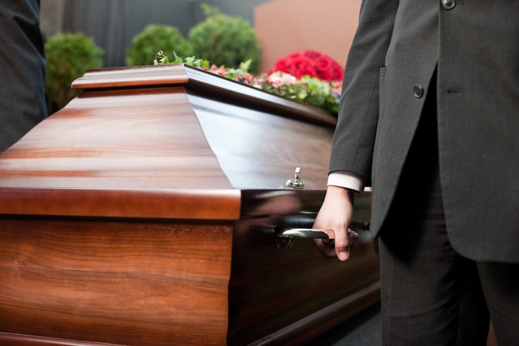 coffin bearer carrying casket at funeral to cemetery