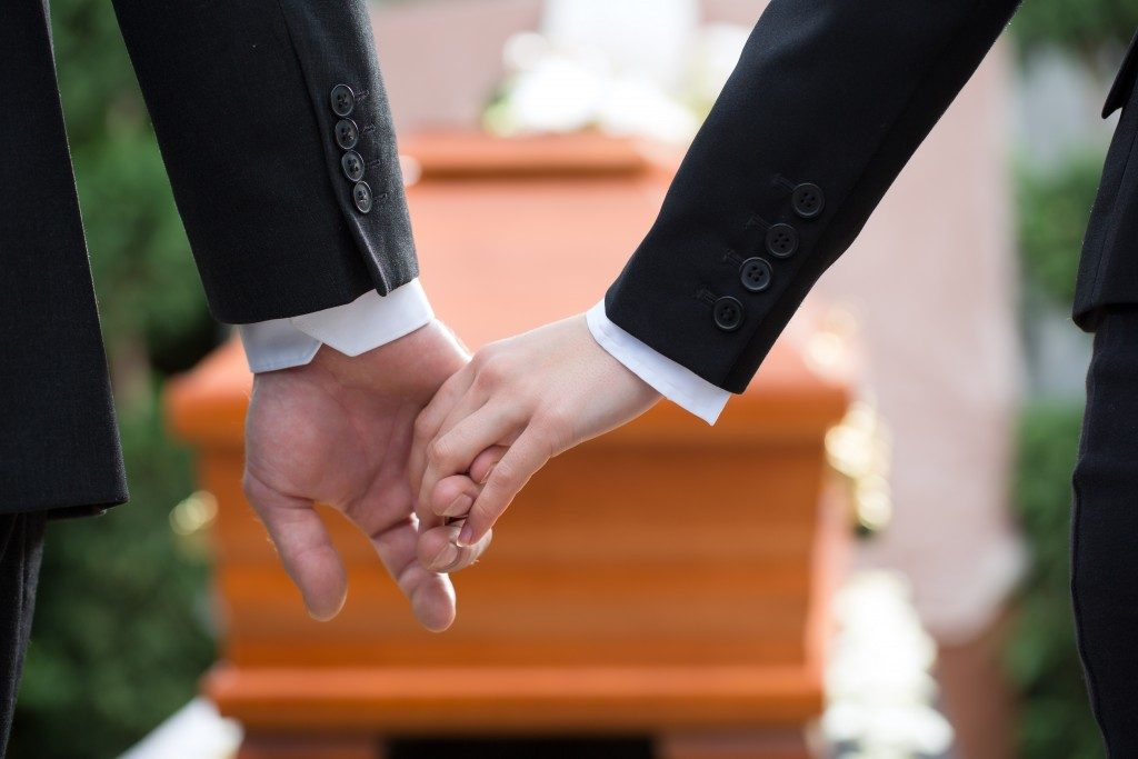 two people holding hands in the middle of funeral