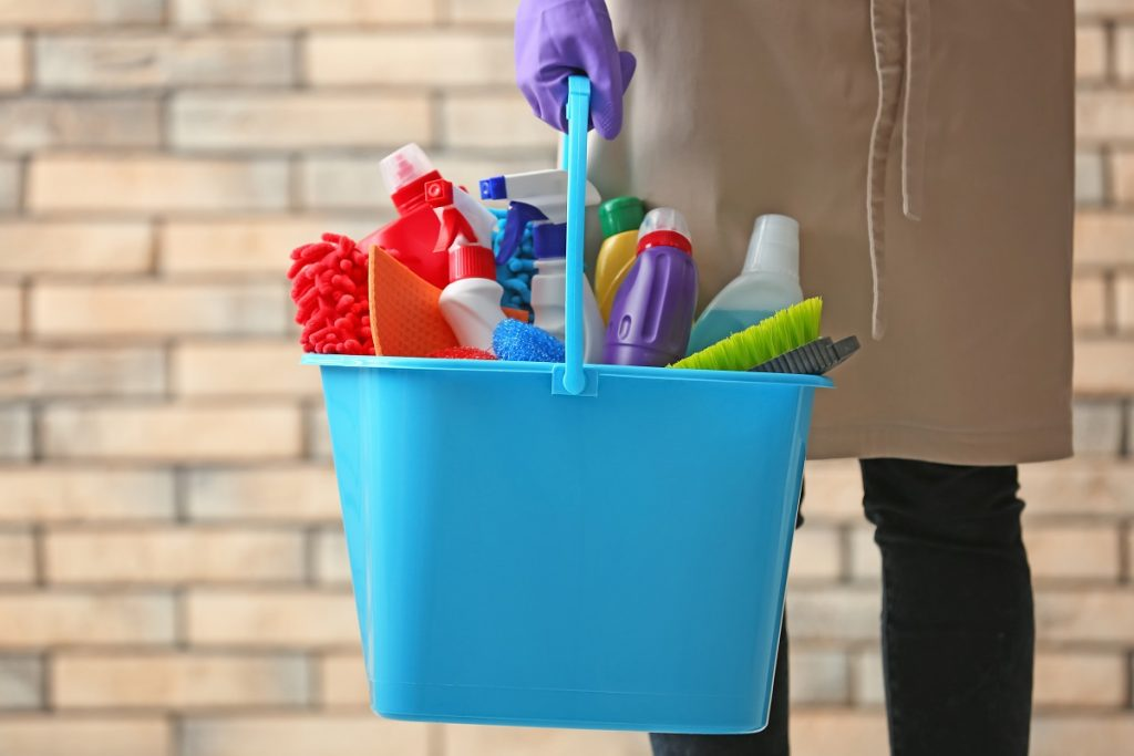 person holding a container full of cleaning tools