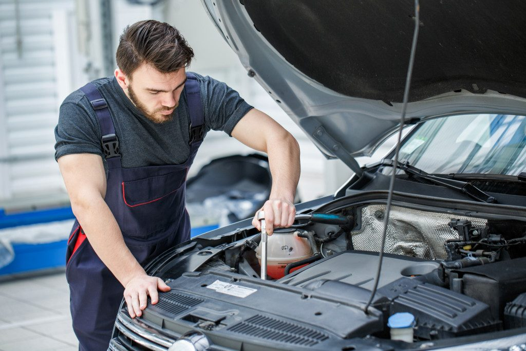 Man checking car engine